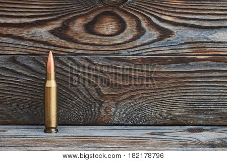 Full metal jacket bullet on wooden background with copy space