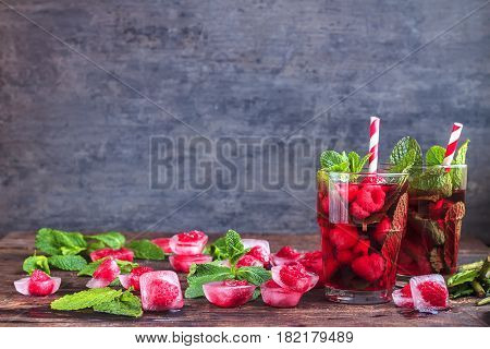 Frozen raspberry in cube of ice with mint on grunge background. Frozen fruit. Top view, close up. Free space for text
