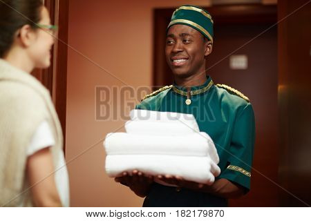Happy hotel servant giving clean towels to one of guests