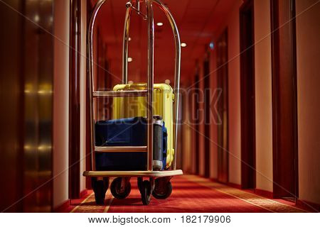 Cart of porter with suitcases in aisle of hotel