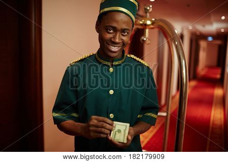 Happy hotel staff counting payment for his service