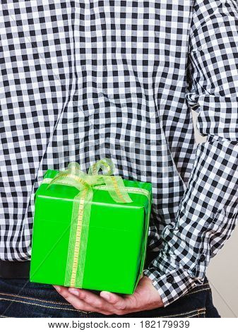 Man hiding green gift box with white ribbon behind back. Closeup of male hand holding christmas present. Guy wearing flannel shirt. Birthday holiday surprise.