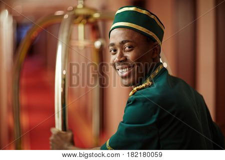 Smiley young bellboy pushing cart with luggage