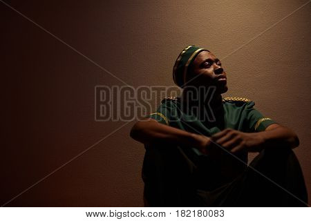 Young African-american bellboy sitting by wall of hotel