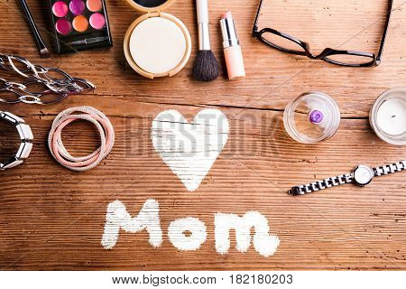Mothers day composition. Various beauty products laid on table. Studio shot on wooden background. Flat lay.