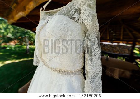 Beautiful lace top of wedding dress hanging on the wooden arbor outdoors