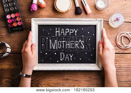 Hands of unrecognizable woman holding white picture frame with Happy mothers day sign. Various beauty products laid on table. Studio shot on wooden background. Flat lay.