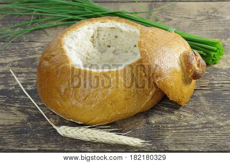 empty bread bowl with a lid on wooden background