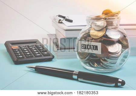 Money Saving For Education Fee Or School Free In The Glass Bottle With Book And Pen On Blue Backgrou