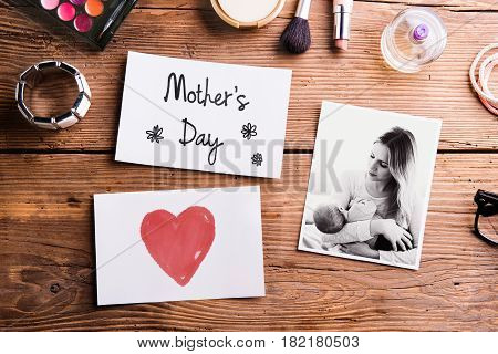 Mothers day composition. Mother and baby picture, note and various beauty products laid on table. Studio shot on wooden background. Flat lay.
