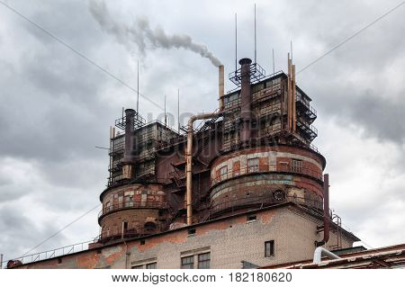 Old sulfuric acid plant on the background of a cloudy sky. Focus on the right tower