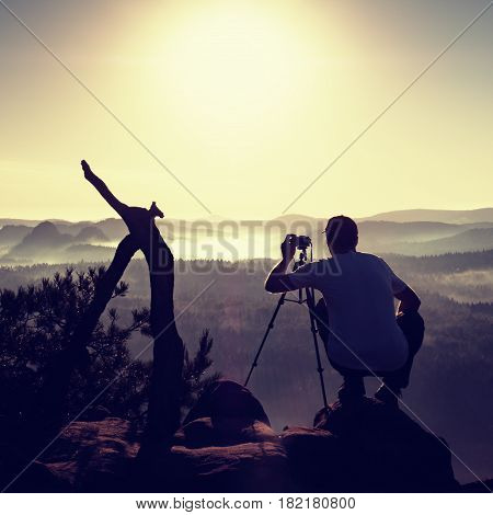 Nature Photographer With Tripod And Camera On Cliff And Thinking
