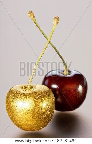Cherries isolated on a gray background, decorated with gold