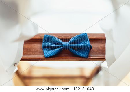 Blue white bow tie on a wooden background. Accessory for formal dress. Symbol of elegance and fashion for men. Men's casual. Men's and women's accessories.