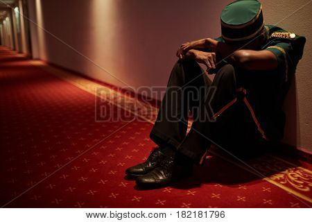 Tired hotel servant sitting by wall in hotel corridor