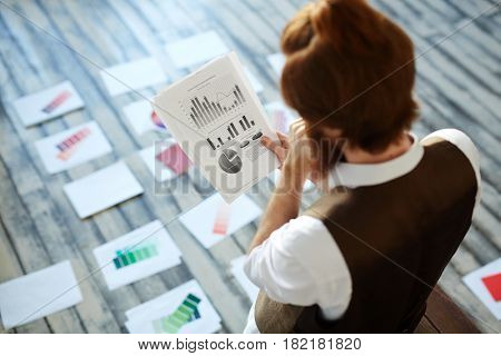 Pensive specialist looking at chart on paper