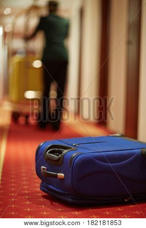 Blue suitcase on the floor of hotel by the door of room