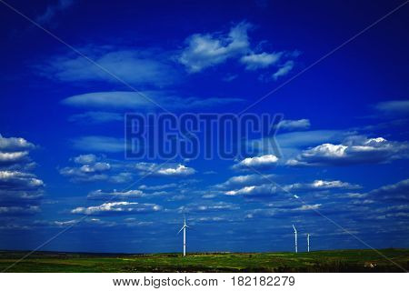 wind turbnes on a summer field and blue sky