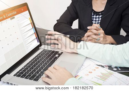 business hand typing on a laptop keyboard with Calender Planner homepage on the computer screen. organization management remind concept.