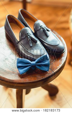 Blue shoes and bow tie on a wooden round stool. Accessory for formal dress. Symbol of elegance and fashion for men. Men's wedding accessories.