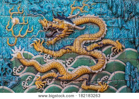 Flying yellow imperial dragon with waves, clouds and silhouettes of mountain on the famous nine dragon wall in the Forbidden city in Beijing