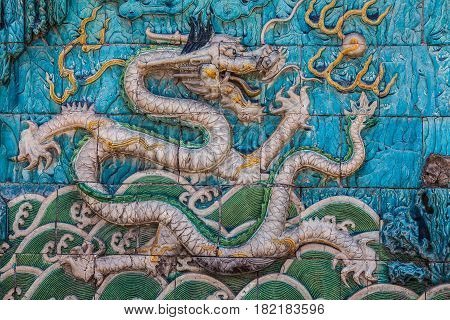 White imperial dragon with green crest and long curved tail on the famous nine dragon wall in the Forbidden City in Beijing
