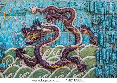 Flying purple dragon with forepaws in waves and tail in clouds on the nine dragon wall in the Forbidden City in Beijing