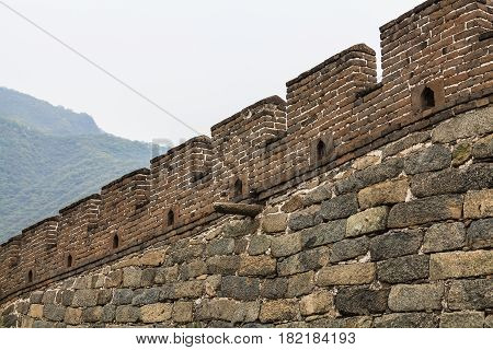 Close up of granite section of the Great Wall of China with battlements and ancient stone drainage