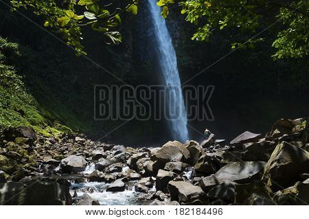 View of the La Fortuna Waterfall with one man standing on a rock in Costa Rica Central America; Concept for travel in Costa Rica