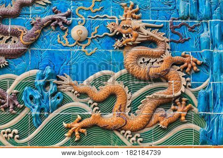 Yellow dragon playing with pearl among waves and clouds on the famous Nine dragon wall in the Forbidden City in Beijing