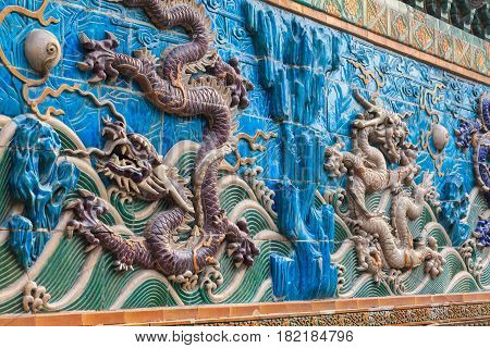 Flying purple and white dragons relief figures on stormy waves pattern. Close  up of the Nine dragon wall in the Forbidden City in Beijing