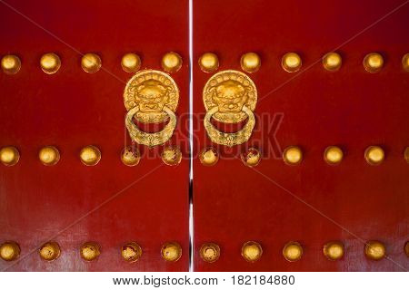 Ancient chinese gate red doors with golden rivets and dragon heads knockers adorned traditional ornaments