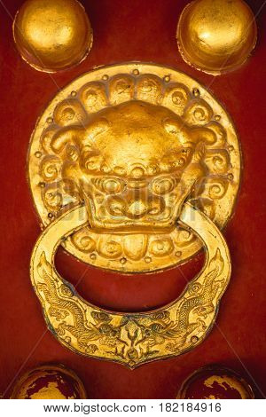 Close up golden dragon head door knob with traditional chinese ornaments on old red temple gate