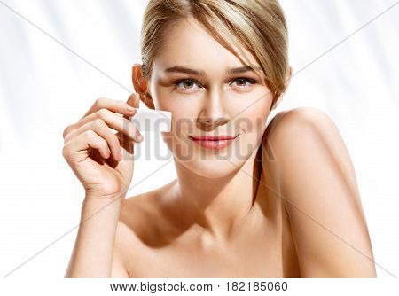 Gorgeous woman applying foundation on her face using makeup sponge. Beautiful woman face on white background. Perfect makeup