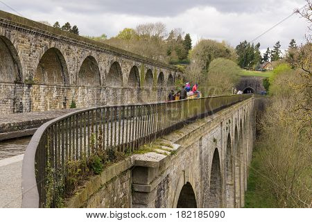 Chirk United Kingdom - April 15 2017: Narrowboat and walkers crossing the aqueduct on the Llangollen canal built in 1801 with the railway viaduct and Chirk tunnel entrance in the background