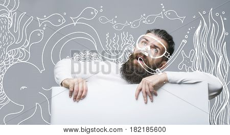 bearded man long beard brutal caucasian hipster with moustache on surprised face at white paper sheet with painted underwater fish diving mask on grey background copy space