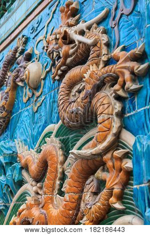 Detailed fragment of the Nine dragon wall in Beijing depicting yellow dragon figure among waves and clouds made from glazed tiles