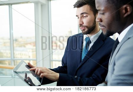 Businessman pointing at data in touchpad and explaining it