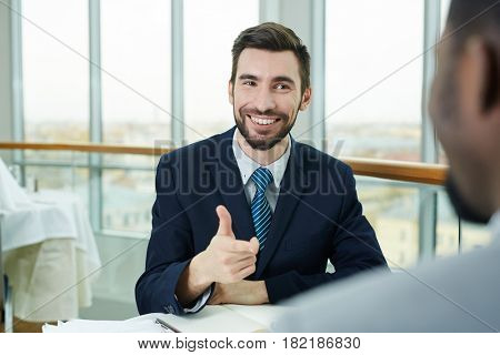 Smiing employer pointing at business partner during talk
