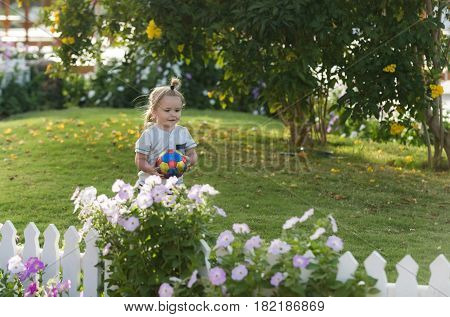 Happy Cute Baby Boy Playing With Ball On Green Grass