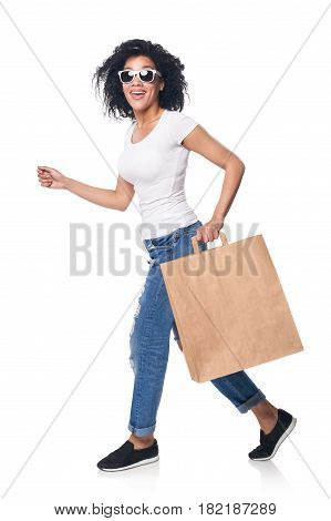 Full length happy mixed race woman holding craft shopping bag with empty copy space running hurrying isolated on white background