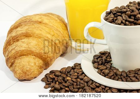 Cup of coffee filed with coffee beans with croissants and orange juice on white background close
