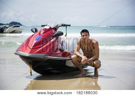 Young muscular male sitting on sand and posing near wave runner on background of beach.