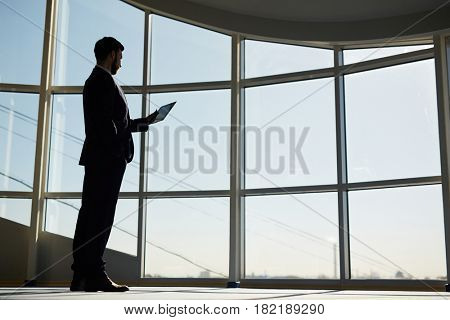 Modern businessman with touchpad networking inside office building