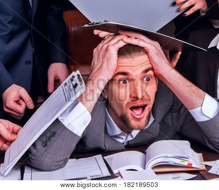 Business people office. Team people are unhappy with their leader. Intern man manager littered with work and does not cope with his duties. Businessman in stress.