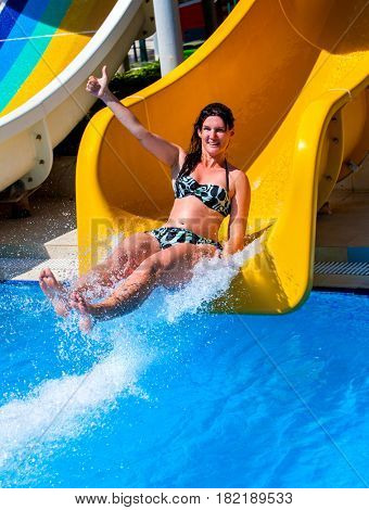 Swimming pool slides for adults on blue water slide at aquapark . Summer woman ride holiday outdoor. Happy beautiful girl in swimsuit with thumb up in aqua park. Good weather in hotel.