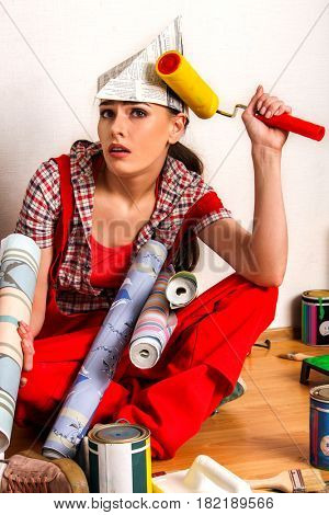 Repair home woman holding paint roller for wallpaper. Tired and frustrated female in newspaper cap renovation apartment. Paint bank and roll paper background on isolated.