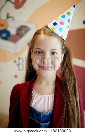 Pretty youngster with ponytails wearing birthday-cap