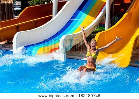 Swimming pool slides for child on blue water slide at aquapark . Summer kids ride holiday outdoor. Happy beautiful girl in yellow swimsuit with hands up in aqua park. Good weather in hotel.