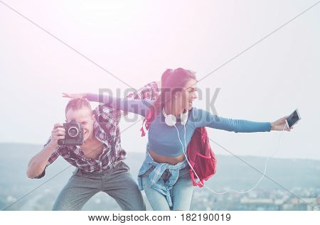 Smiling happy couple pretend flying in sky. Handsome man or photographer photographing with camera. Pretty girl or cute woman with smartphone earphones and backpack. Traveling vacation